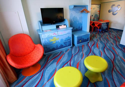 The main living area in Disney's Art of Animation Finding Nemo Suites offers a Flat screen TV, mini kitchenette and a dining table for 6 that converts to a double bed at night