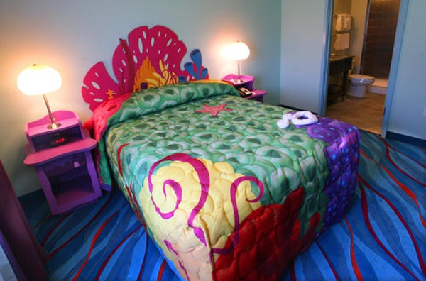 The colorful master bedrooms at Art Of Animation Finding Nemo have a door for privacy, Queen size bed, Flat Screen TV and full bath with a shower
