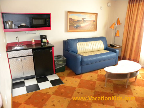 Main living area at Disney's Art of Animation Cars family suite offers a mini kitchenette and a double bed sleeper sofa