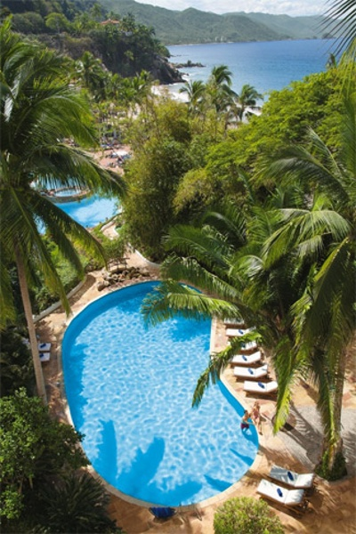 View of adult pool amidst palms and mountains at Dreams Puerto Vallarta Resort & Spa