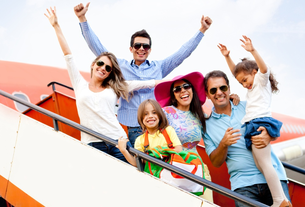 Excited family with arms up traveling by airplane-1
